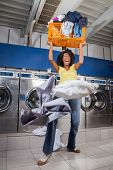 foto of laundromat  - Young woman screaming while carrying overloaded laundry basket at laundromat - JPG