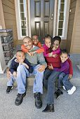 stock photo of nuclear family  - African family sitting on front steps - JPG