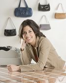 image of boutique  - Hispanic businesswoman behind counter at boutique - JPG