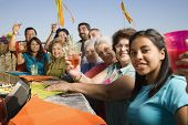 foto of niece  - Large Hispanic family toasting at party outdoors - JPG