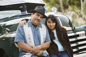 stock photo of pre-adolescent child  - Hispanic father and daughter sitting on classic car - JPG