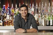 foto of bartender  - Hispanic male bartender leaning on bar - JPG