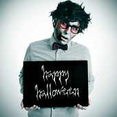 pic of nerd glasses  - a hipster zombie showing a black signboard with the text happy halloween written in it - JPG