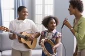 stock photo of pre-adolescent child  - African American mother and children playing instruments - JPG