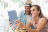 foto of latte coffee  - Happy couple enjoying coffee using tablet at the coffee shop - JPG