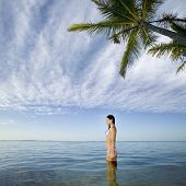 stock photo of pacific islander ethnicity  - Pacific Islander woman standing in ocean - JPG