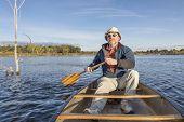picture of collins  - senior male enjoying morning sun on lake in a canoe - JPG