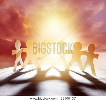 Team of six paper chain people holding hands in front of bright sky
