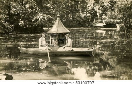 BERLIN, GERMANY, CIRCA 1930's: Vintage photo of two women rowing in boat at small lake