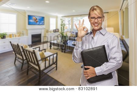 Smiling Real Estate Agent with Okay Sign in Living Room of New House.