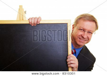 Teacher Hiding Behind Blackboard