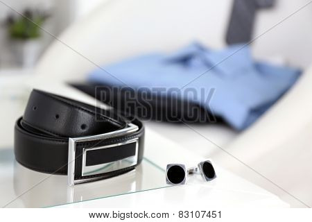 Men's belt and cufflinks on coffee tablewith shirt and tie on chair on background