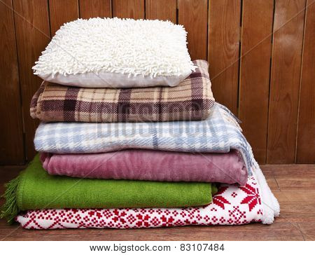 Pile of plaids and pillows on rustic wooden background