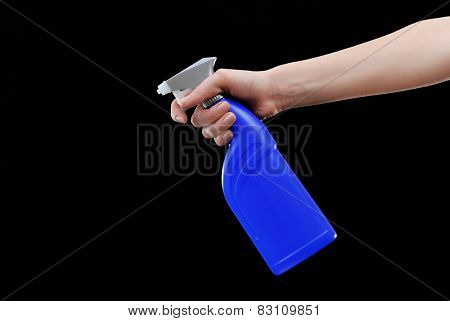 Male hand with sprayer on black background