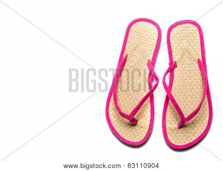Straw and pink flip-flop sandals on a white background with copy space