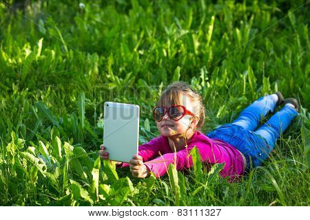 Little funny girl with a tablet makes a self-portrait (selfie) lying in the green grass.