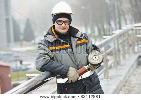 industrial builder worker with ggrinder polishing metal barrier