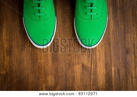 Colorful green sneakers on wooden background.