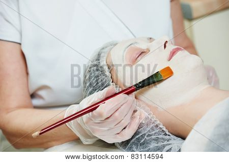 beautician worker with paintbrush applying facial cosmetic mask to female client in beauty salon