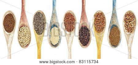 a collection of gluten free grains and seeds on isolated wooden spoons - kaniwa, sorghum, chia, amaranth,red quinoa, black quinoa, brown rice, teff, buckwheat  (from left to right)