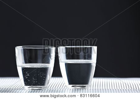 Two glasses of water on table on dark background