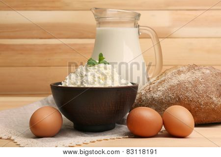 Cottage cheese in clay bowl with jug of milk,eggs and loaf of bread on wooden planks background