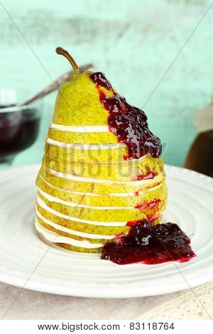 Tasty dessert with pear, cream and berry sauce on plate, on color wooden background