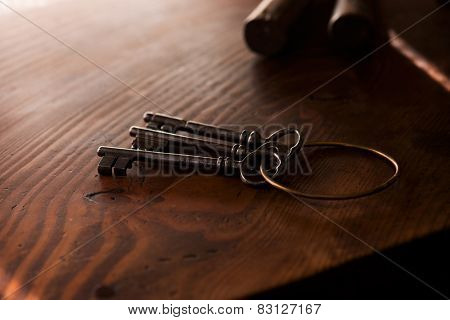 Vintage keys on an grungy old desk in light and shadow. Shallow depth of focus.