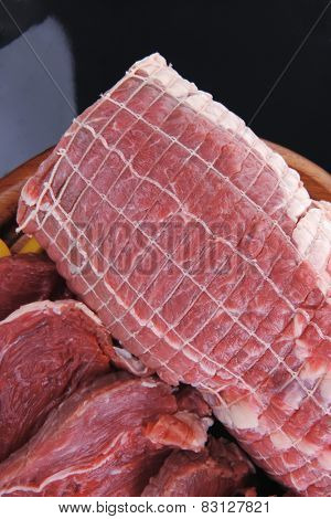 fresh raw meat on wooden board with slices