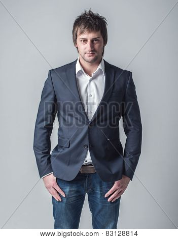 Young confident man formal clothes classic jacket and denim jeans gray background.