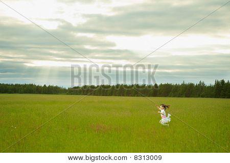 Little Girl In Dress Runs On Meadow