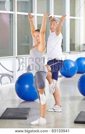 Two happy senior people exercising together in a gym