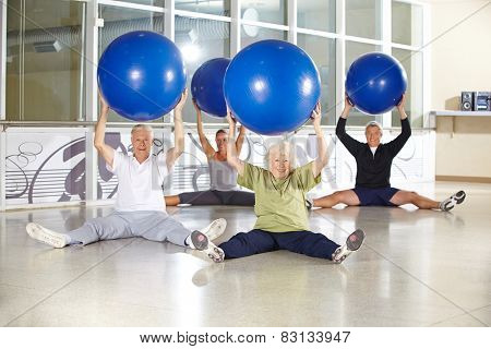 Group of senior people with gym balls in fitness center doing back training exercises