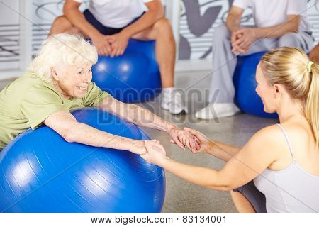Happy senior woman with fitness instructor in rehab center