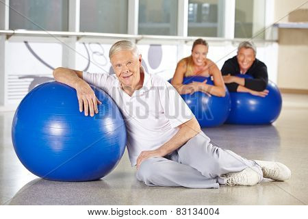 Elderly man exercising with gym ball in health club for rehab