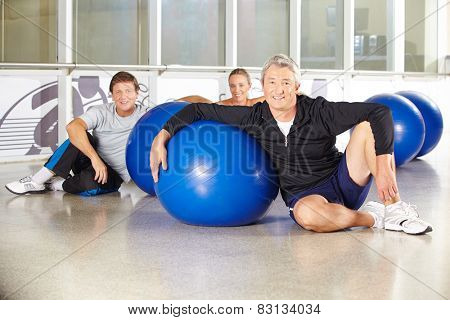 Man sitting in group of senior people with gym ball in a fitness center
