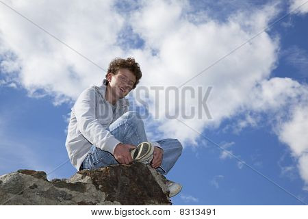 smiling teenager sitting on a wall