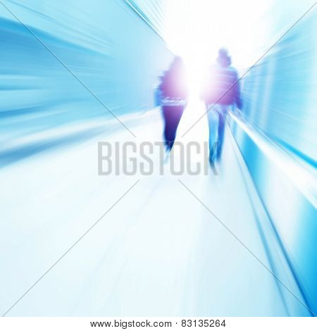 Toned image of motion blurred people walking to light.