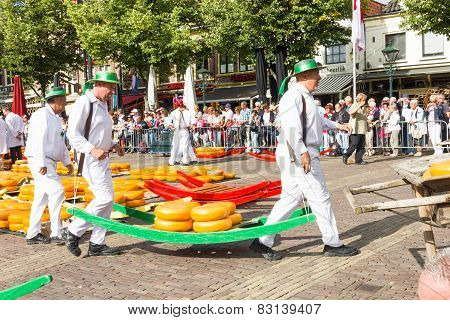 Carriers walking with many cheeses in the famous Dutch cheese market, Alkmaar