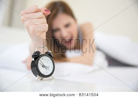 Young angry girl who woke up very early to call an alarm clock in the bedroom. Focus on clock