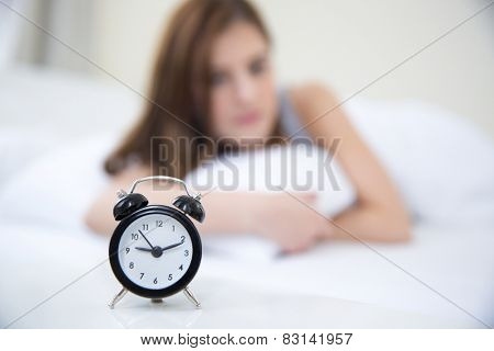 Woman waking up in the morning and looking on alarm clock. Focus on clock