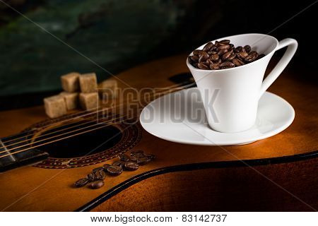Coffee Cup And Cane Sugar On A Guitar