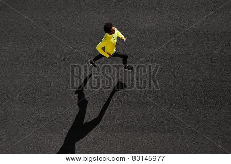 Top View Athlete Runner Training At Black Road In Yellow Sportswear At Central Position. Muscular Fi