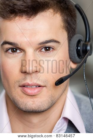 Closeup portrait of confident male call center employee wearing headset in office