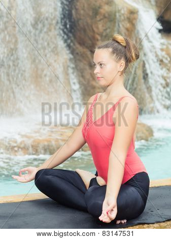 Woman practicing yoga near waterfall. Accomplished Pose. Siddhasana