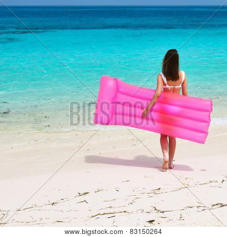 Woman with pink inflatable raft walking at the beach