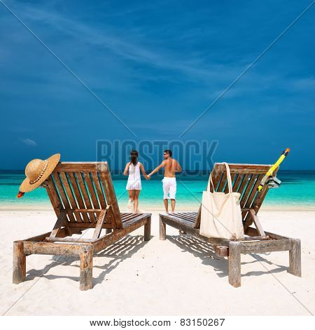 Couple in white running on a tropical beach at Maldives