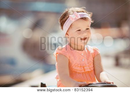 Little girl having fun on the waterfront in the summer.
