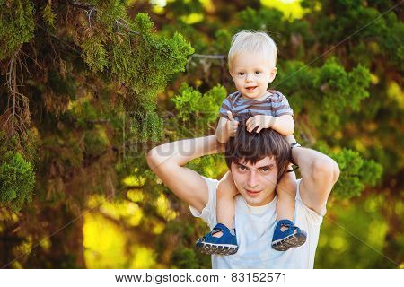 Father and young son having fun and having fun in the summer park.