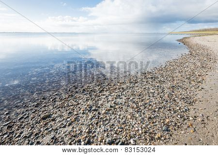 Cloudy Sky Reflected In The Mirror-smooth Surface Of The Water